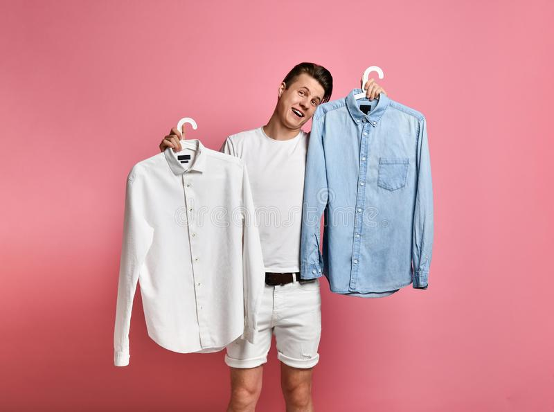 Young man makes a choice of a shirt. Blue or white? what choose?. On a pink background stock photo
