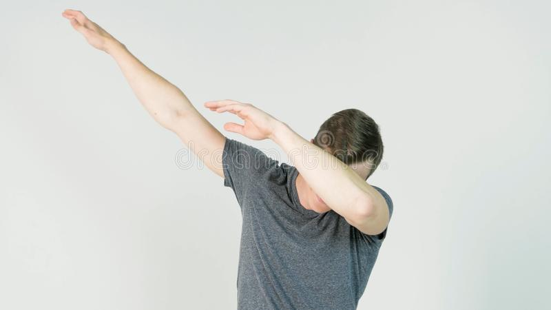 Young man makes a dab or flex it`s dance move on white background stock photography