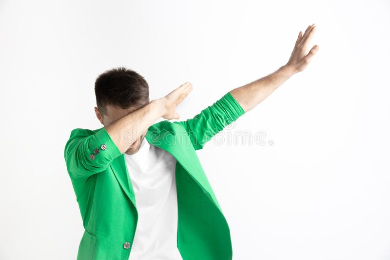 Young man makes the dab movement with his arms on a gray background. Young man makes a dab movement with his arms on a gray background. Human emotions, facial stock photos