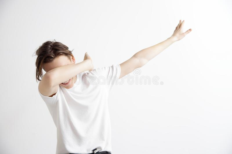 Young man makes the dab movement with his arms on a gray background. Young man makes a dab movement with his arms on a gray background. Human emotions, facial royalty free stock image