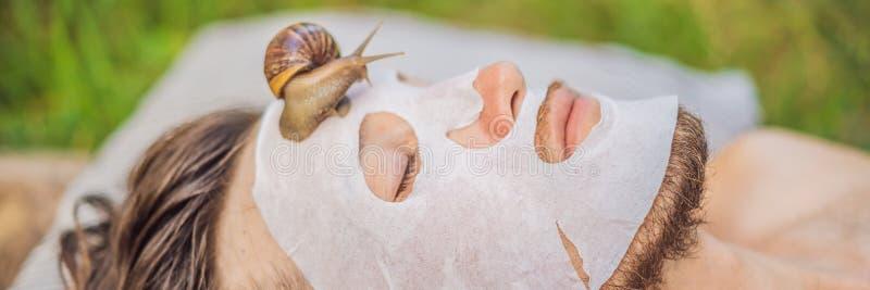 Young man makes a face mask with snail mucus. Snail crawling on a face mask. SPA for man, SPA for all BANNER, LONG. Young man makes a face mask with snail mucus stock photos