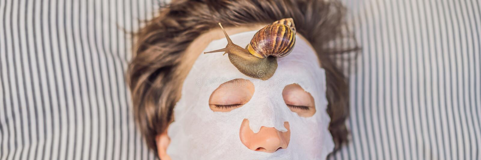Young man makes a face mask with snail mucus. Snail crawling on a face mask. SPA for man, SPA for all BANNER, LONG. Young man makes a face mask with snail mucus royalty free stock photo