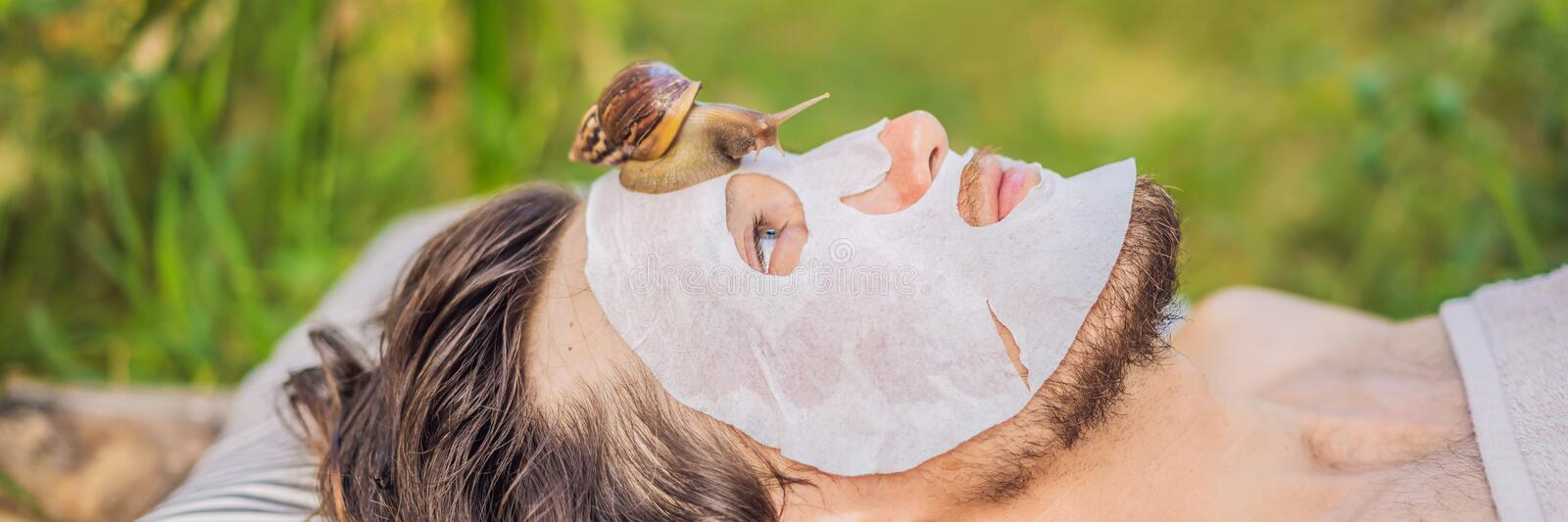 Young man makes a face mask with snail mucus. Snail crawling on a face mask. SPA for man, SPA for all BANNER, LONG. Young man makes a face mask with snail mucus stock photography