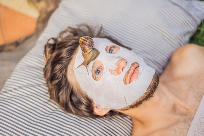 Young man makes a face mask with snail mucus. Snail crawling on a face mask. SPA for man, SPA for all.  royalty free stock photo