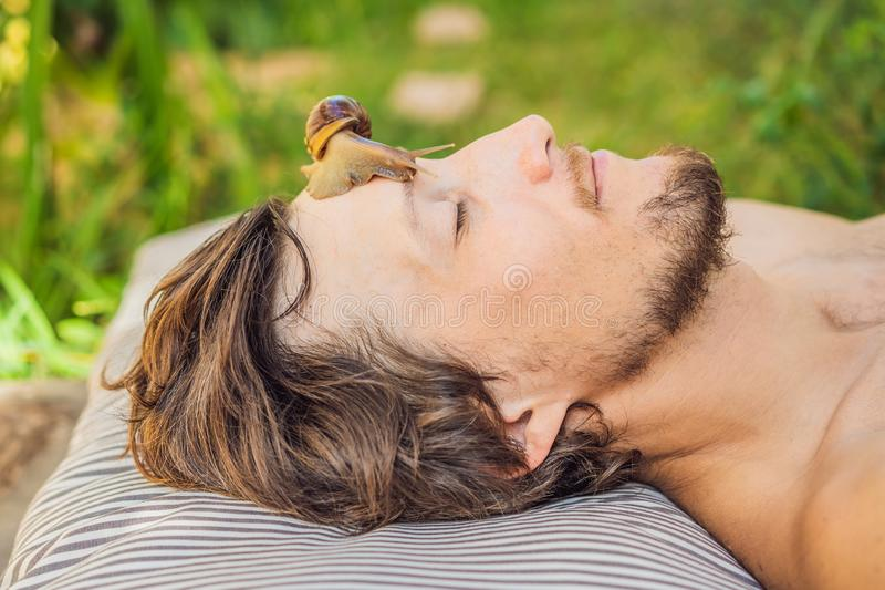 Young man makes a face mask with snail mucus. Snail crawling on a face mask. SPA for man, SPA for all.  stock image