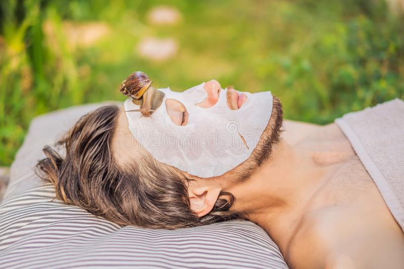 Young man makes a face mask with snail mucus. Snail crawling on a face mask. SPA for man, SPA for all.  stock photo