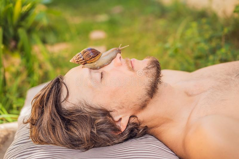 Young man makes a face mask with snail mucus. Snail crawling on a face mask. SPA for man, SPA for all.  royalty free stock photos