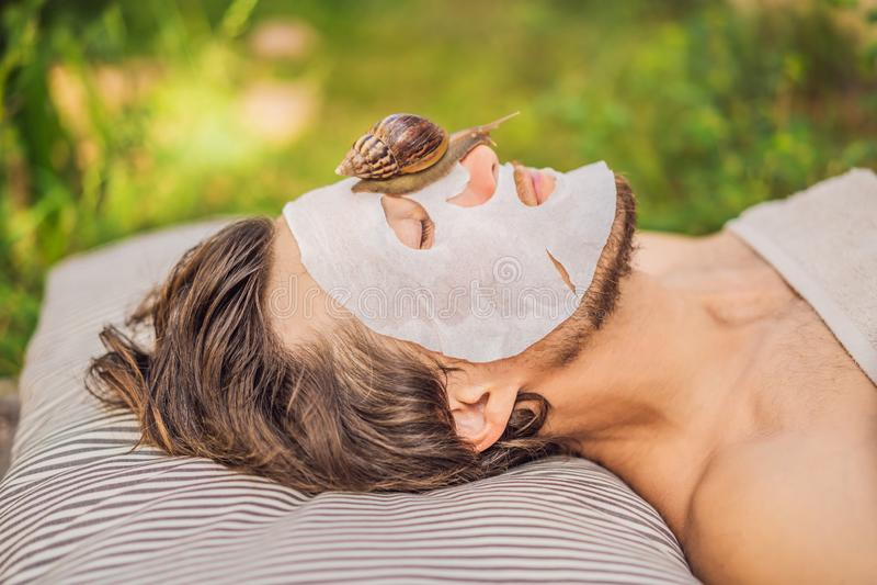 Young man makes a face mask with snail mucus. Snail crawling on a face mask. SPA for man, SPA for all.  stock photos