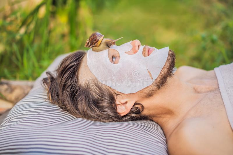 Young man makes a face mask with snail mucus. Snail crawling on a face mask. SPA for man, SPA for all.  royalty free stock photography