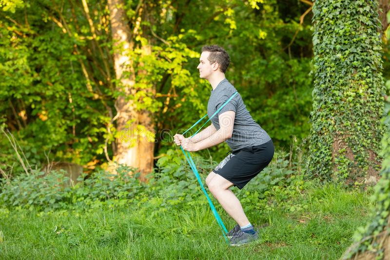Young man makes fitness exercises in nature stock photography