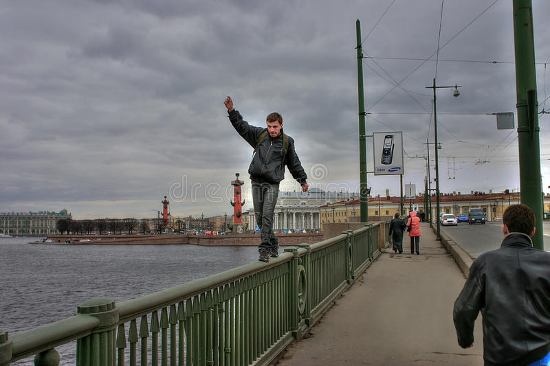 Young man makes life threatening walk on parapet of bridge. St. Petersburg, Russia - April 22, 2006: Unidentified man risked his life to pass on parapet royalty free stock image