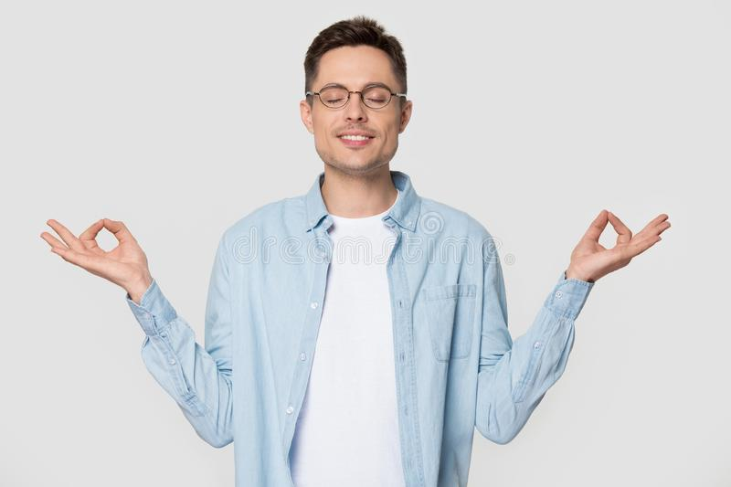 Young man makes mudra gesture meditates standing over grey background royalty free stock photography