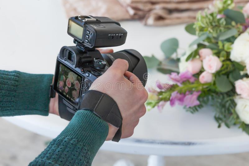 A young man makes a photo of a wedding bouquet, a picture on the camera screen royalty free stock photos