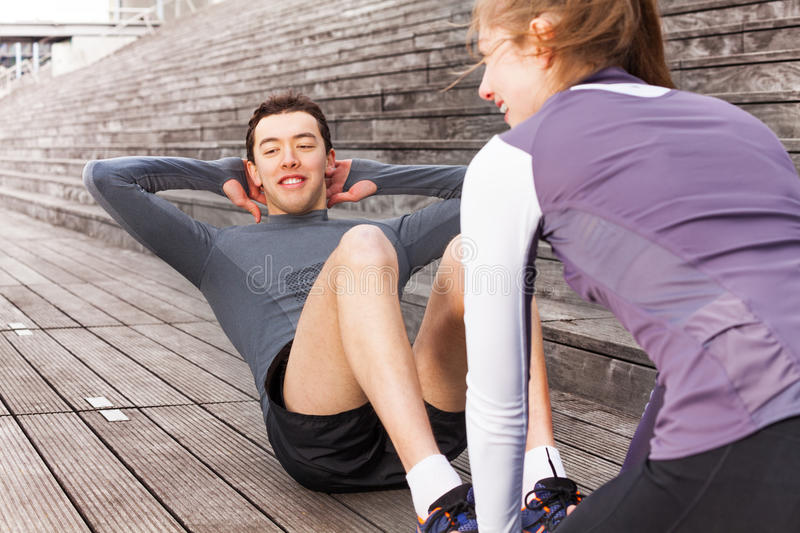 Young man making abs exercises outdoors with coach stock image