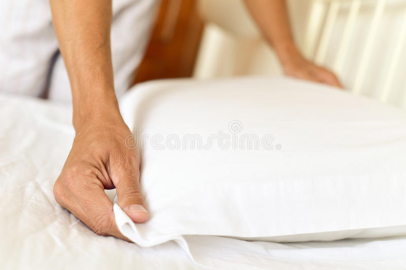 Young man making the bed royalty free stock photo