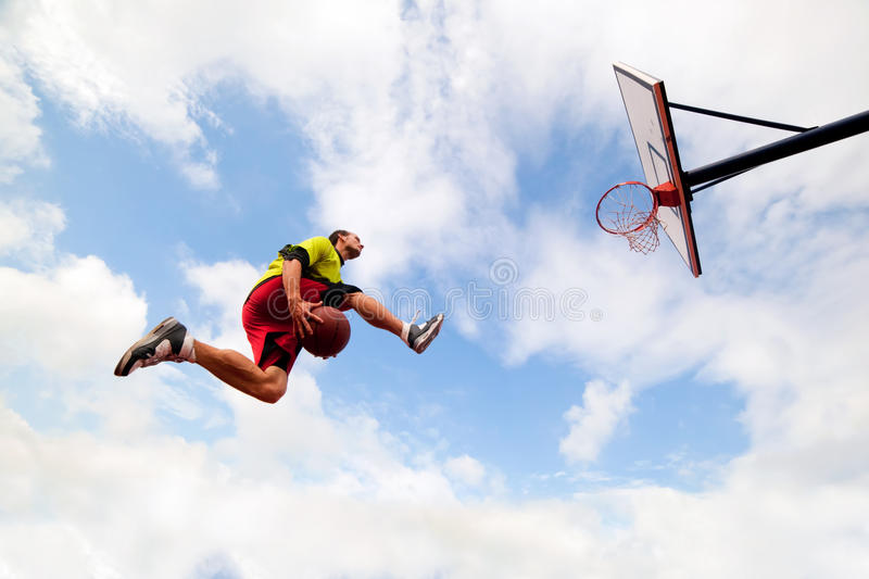 Young man making a fantastic slam dunk playing basketball. Young man jumping and making a fantastic slam dunk playing streetball, basketball. Urban authentic royalty free stock image