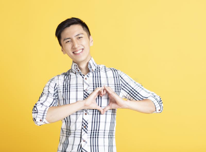 Man making heart gesture on his chest. Young man making heart gesture on his chest stock image