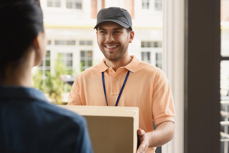 Young man making home delivery stock photography