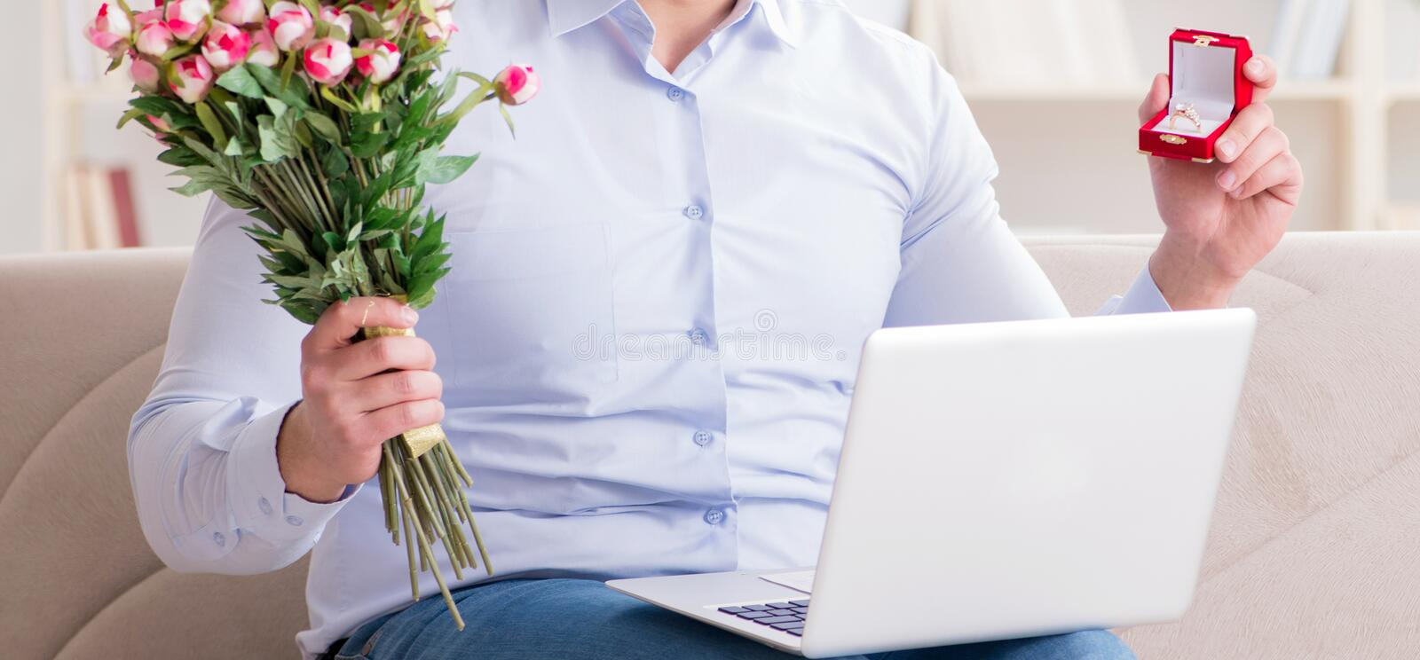 Young man making marriage proposal over internet laptop stock images