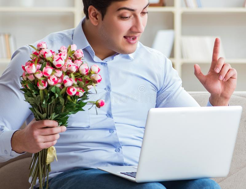 Young man making marriage proposal over internet laptop stock image