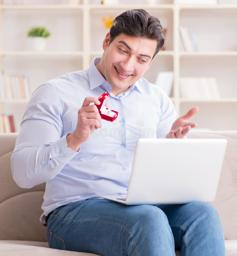 The young man making marriage proposal over internet laptop stock photography