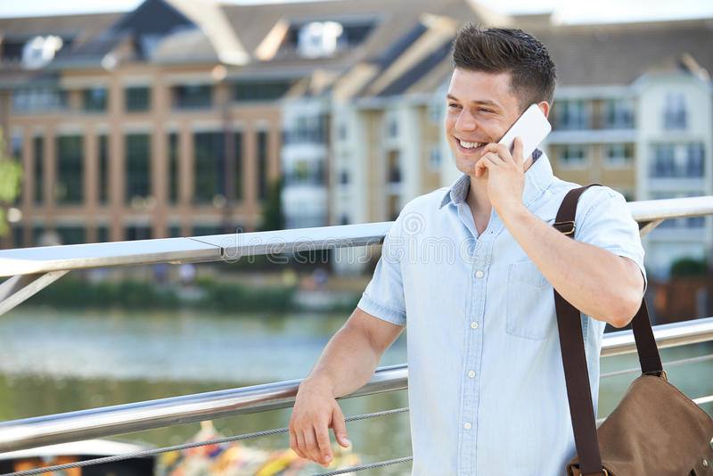 Young Man Making Phone Call On Mobile Phone Walking To Work stock photo