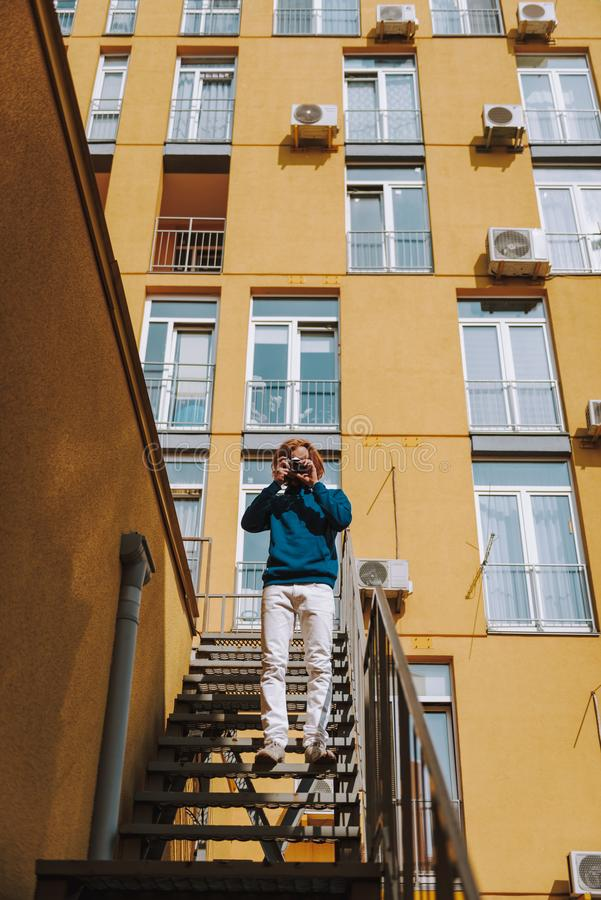 Young man making photo on camera on stairs. Urban lifestyle concept. Full length low angle portrait of young red haired hipster guy making photo on camera while royalty free stock photo
