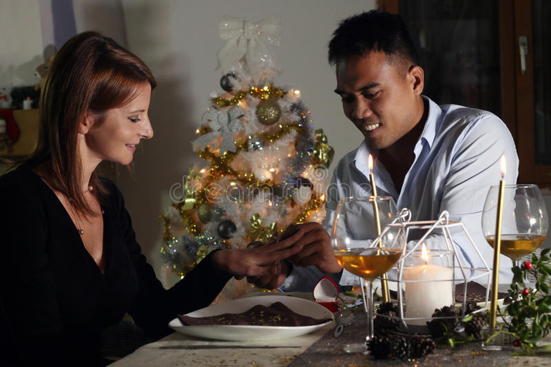Young man making a proposal for marriage at Christmas. Asian men making a proposal for marriage at Christmas diner royalty free stock images