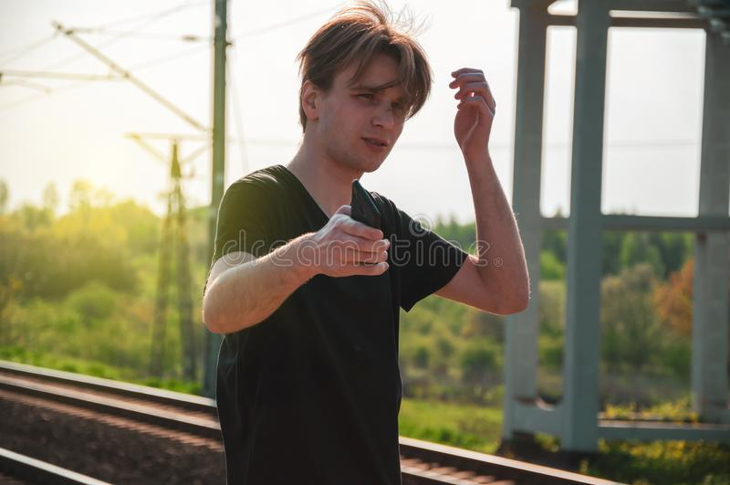 Young man making sad face and gestures pointing at the train that has left earlier. Man is late for train, latecomer stock photos