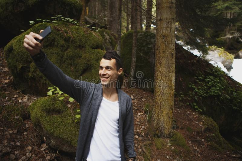 Young man making selfie on the background of landscape stock photo