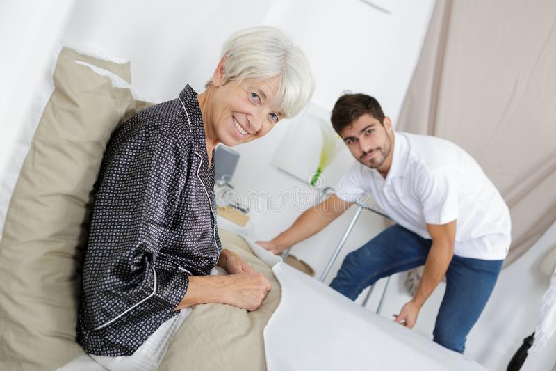 Young man making senior womans bed stock photos
