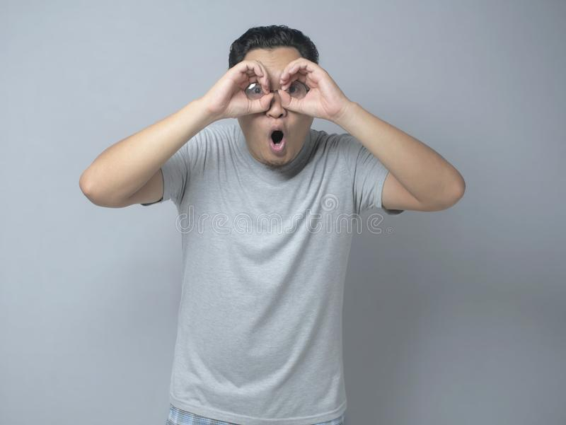 Young Man Making Telescope Gesture With His Hand, Shocked Expression. Portrait of young Asian man making telescope gesture with his hands, shocked surprised royalty free stock photos