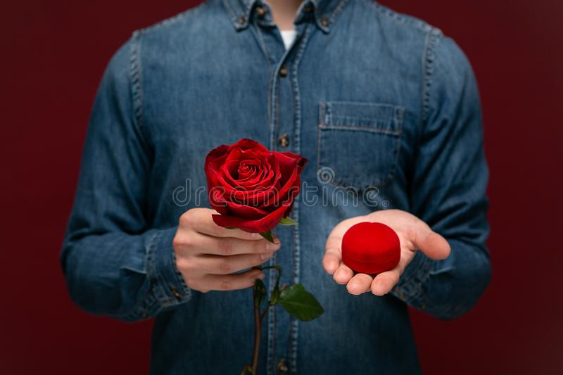 Young man making wedding proposal holding one red rose and box with engagement ring stock images