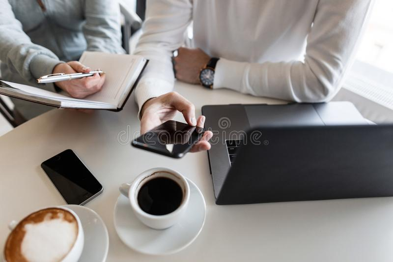 Young man manager sits with a phone in hands and shows his colleague a business plan for a new creative project. stock photos