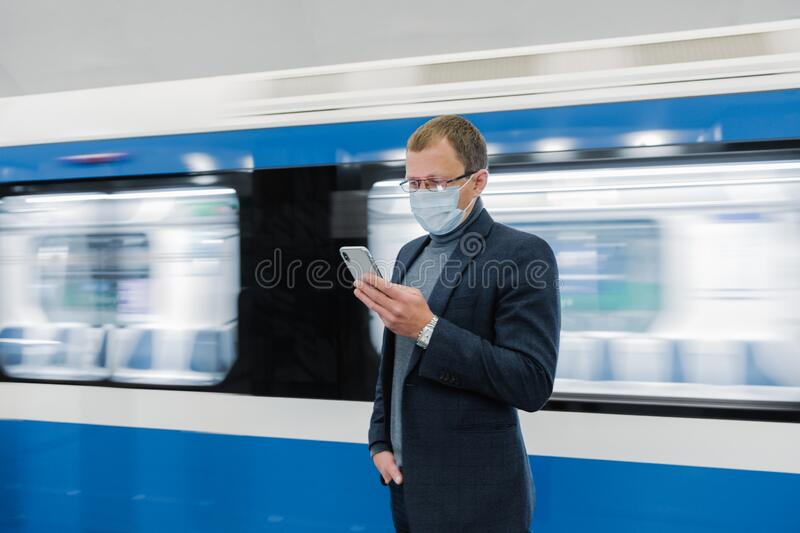 Young man manager uses cellphone, prevents spreading of Coronavirus, poses against subway train, poses at platform, checks news. Online, wears medical mask stock images