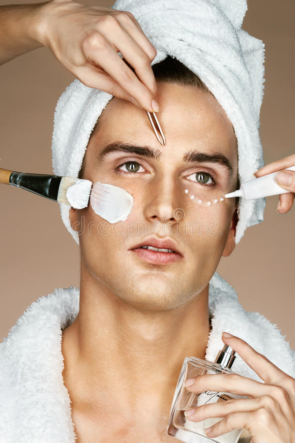 Young man and many hands making different beauty salon services stock photos