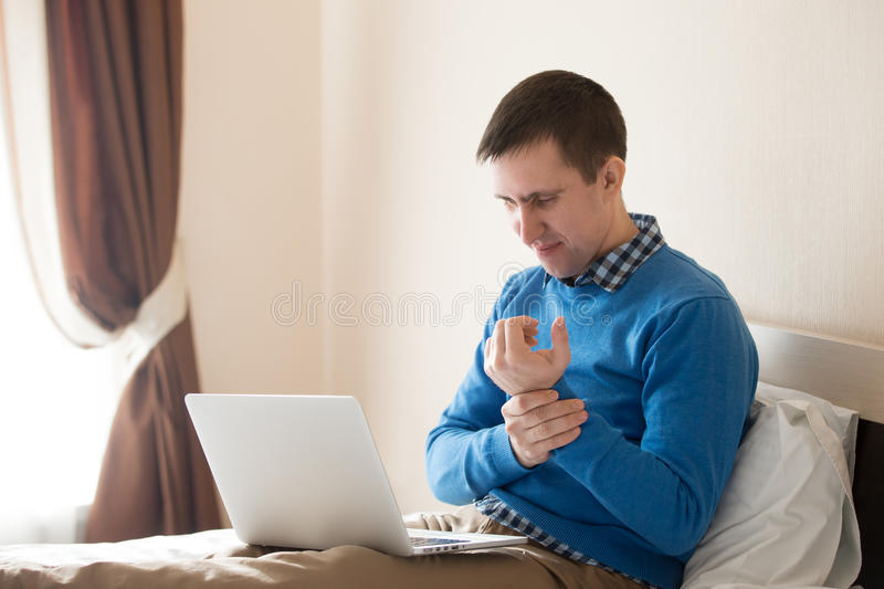Young man massaging his arm stock images
