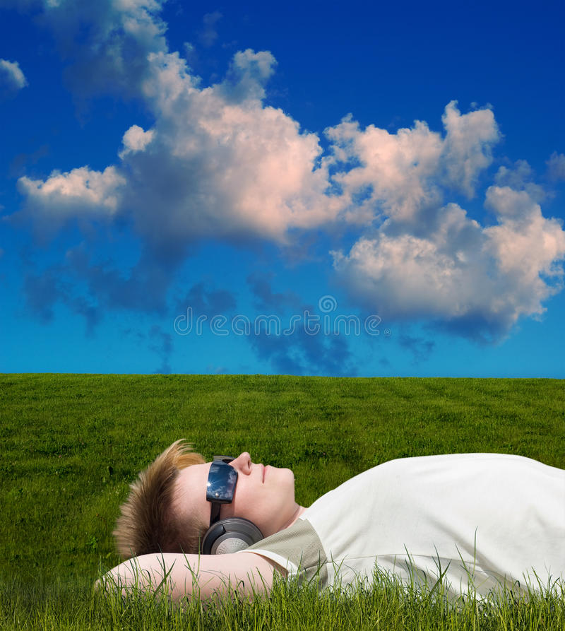 Young man on a meadow. Listening music stock images