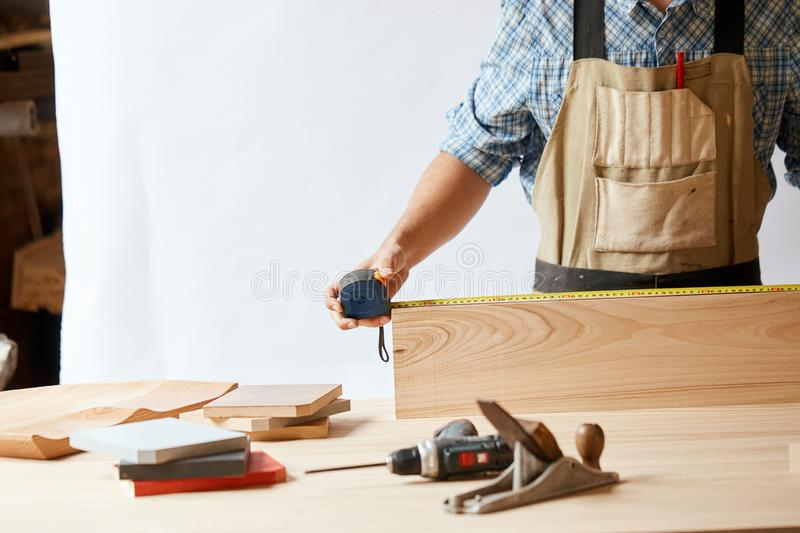 Young man measuring home furniture with measure tape. Repair concept. royalty free stock images