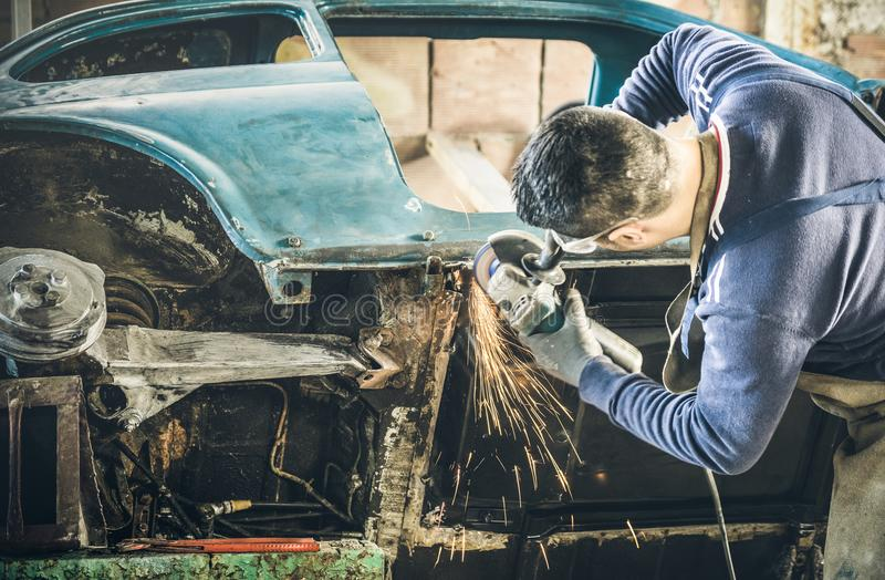 Young man mechanical worker repairing old vintage car body with stock photography