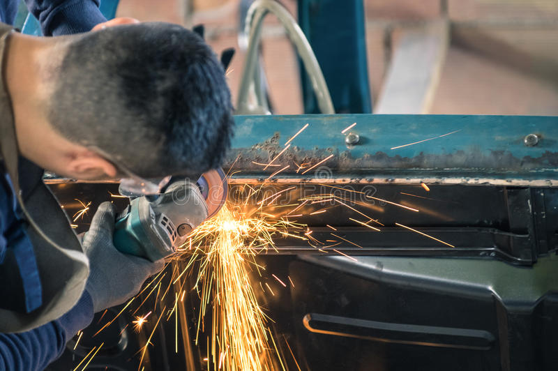 Young man mechanical worker repairing an old vintage car body royalty free stock photos