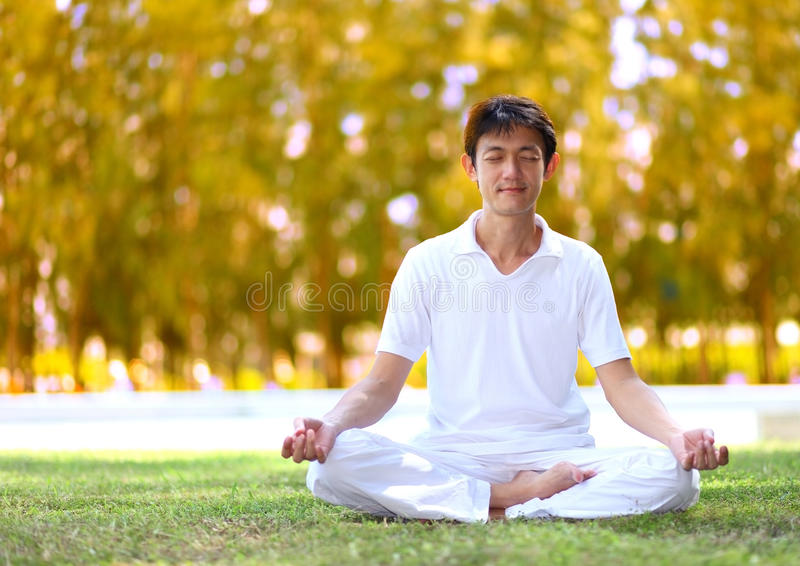 Young man meditating in autumn park. stock image