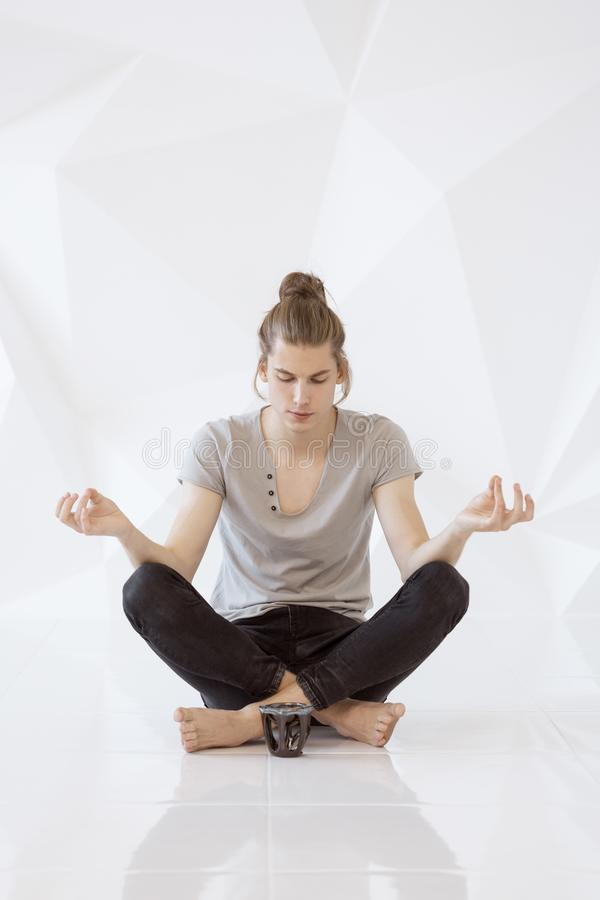 Young man meditating in lotus position stock images