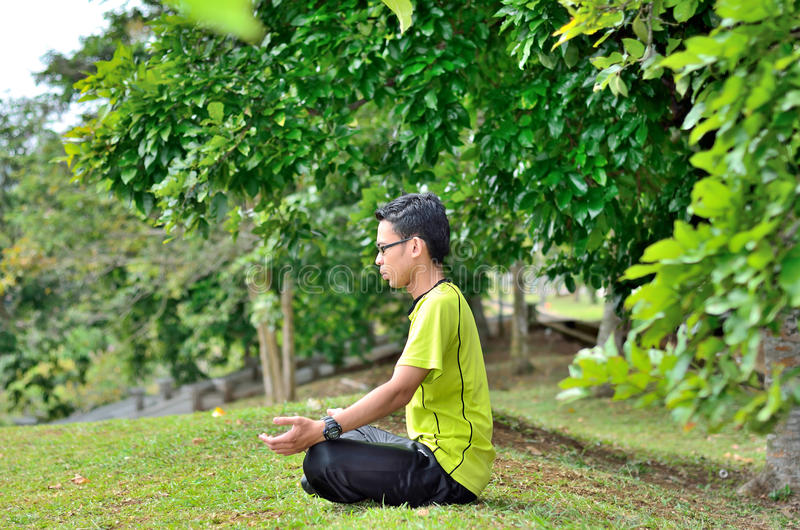 Young man meditating outdoors. With blue sky royalty free stock photography