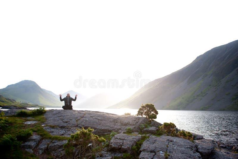 Young man meditating outdoors royalty free stock photos