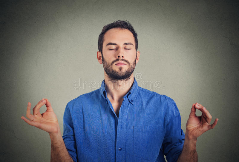 Young man meditating. In zen mode royalty free stock photography