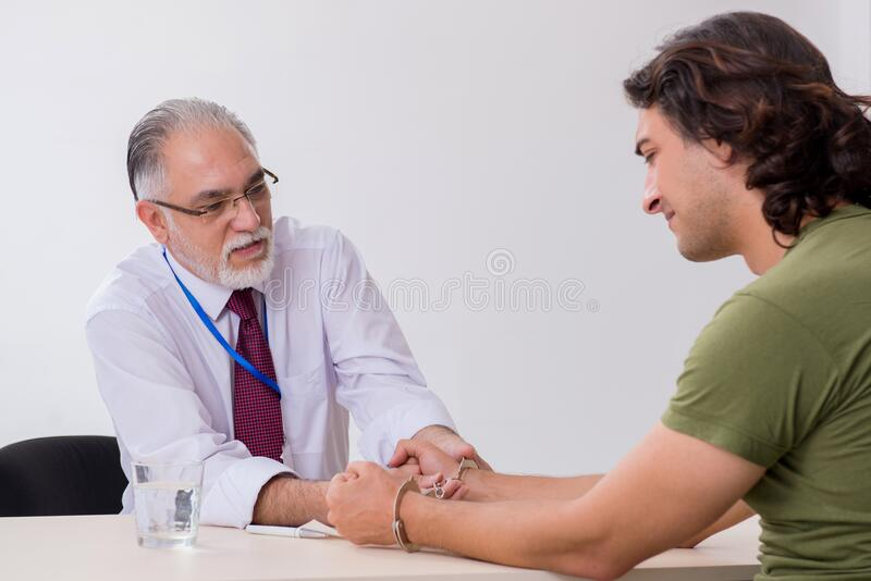 Young man meeting with advocate in pre-trial detention. Young man meeting with advocate in pretrial detention royalty free stock photos