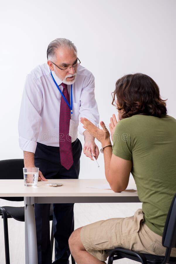Young man meeting with advocate in pre-trial detention. Young man meeting with advocate in pretrial detention stock photo