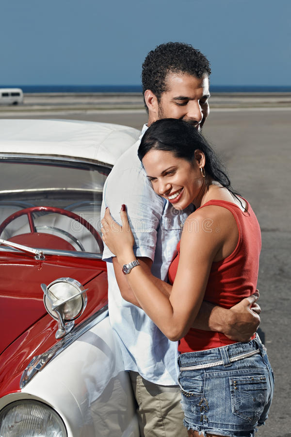 Young man meeting beautiful woman and hugging. Boyfriend and girlfriend leaning on vintage car and hugging in havana, cuba. Vertical shape, side view, copy space stock images