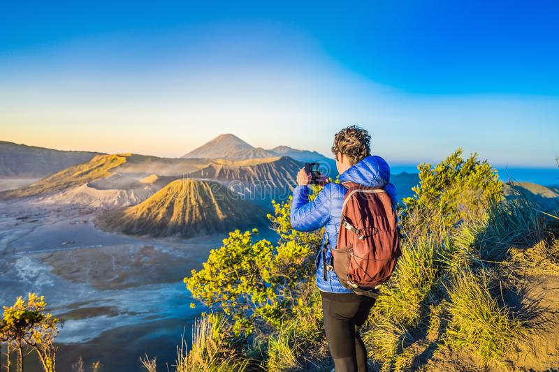 Young man meets the sunrise at the Bromo Tengger Semeru National Park on the Java Island, Indonesia. He enjoys. Magnificent view on the Bromo or Gunung Bromo on royalty free stock photo